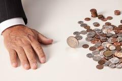 La mano del hombre plana después de lanzar la moneda que está haciendo girar Imágenes de archivo libres de regalías