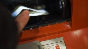 La mano del hombre pone billetes de banco euro en máquina del cajero automático y se cierra con el dinero almacen de video