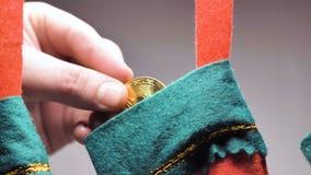 La mano del hombre pone Bitcoin en el primer del calcetín de la Navidad metrajes