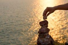 La mano del hombre pone la pirámide de piedras Foto de archivo