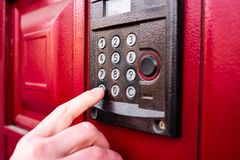 La mano del hombre presiona un timbre o un intercomunicador del botón foto de archivo