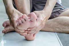 La mano del hombre que es dada masajes un pie fotos de archivo