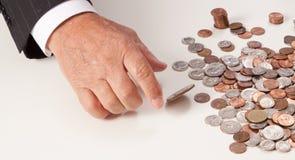 La mano del hombre que escoge la moneda para arriba lanzada Imágenes de archivo libres de regalías