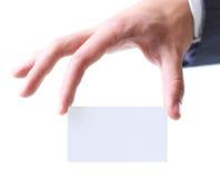 La mano del hombre que guarda una tarjeta de visita entre dos fingeres Imagen de archivo libre de regalías