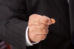 La mano del hombre que pellizca penique-horizontal Fotografía de archivo libre de regalías