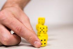 La mano del hombre que se alinea sosteniendo dados amarillos imagen de archivo libre de regalías