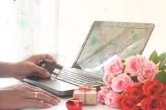 La mano del hombre que sostenía la tarjeta de crédito y que usaba el ordenador con el regalo y subió en la tabla, haciendo compra foto de archivo libre de regalías