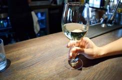 La mano del hombre que sostiene el vidrio de vino blanco Foto de archivo libre de regalías