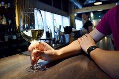 La mano del hombre que sostiene el vidrio de vino blanco Fotos de archivo libres de regalías