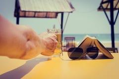 La mano del hombre que sostiene un vidrio de cerveza imagen de archivo