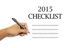 La mano del hombre que sostiene una pluma que escribe una lista de control del Año Nuevo Imagen de archivo libre de regalías