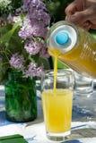 La mano del hombre que vierte el zumo de fruta anaranjado en un vidrio en un GA veraniego Foto de archivo