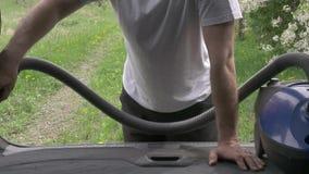 La mano del hombre sostiene el tronco azul del tubo de la aspiradora y del automóvil de los vacíos almacen de metraje de vídeo