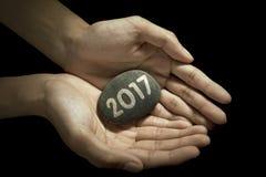 La mano del hombre sostiene la piedra con el número 2017 Imagen de archivo