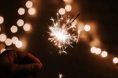 La mano del hombre sostiene las bengalas, Feliz Año Nuevo foto de archivo
