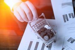 La mano del hombre sostiene un carro de la compra simulado llenado de las monedas imágenes de archivo libres de regalías