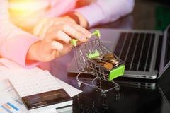 La mano del hombre sostiene un carro de la compra simulado llenado de las monedas imagen de archivo libre de regalías