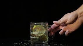 La mano del hombre toma una taza de cristal con té verde Taza de cristal con las hojas de té y la rebanada verdes secas orgánicas almacen de metraje de vídeo