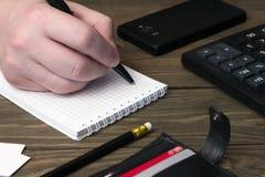 La mano del hombre, un cuaderno con un bolígrafo, cartera Imágenes de archivo libres de regalías