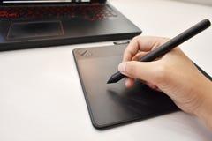 La mano del hombre usando el ratón inalámbrico de la pluma para dibujar fotos de archivo