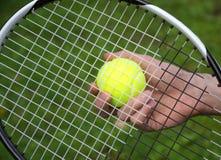 La mano del jugador con la pelota de tenis Imagen de archivo