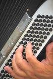 La mano del jugador del acordión en los botones imágenes de archivo libres de regalías