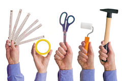 La mano del lavoratore maschio che tiene i vari strumenti di commercio di mestiere Immagini Stock Libere da Diritti