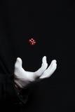 La mano del mago nella rappresentazione bianca del guanto inganna con i dadi Immagine Stock