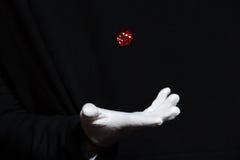 La mano del mago nella rappresentazione bianca del guanto inganna con i dadi Fotografia Stock Libera da Diritti