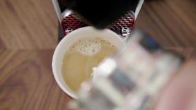 La mano del maschio aggiunge il latte alla tazza rossa con caffè disposto sul vassoio di macchina del caffè stock footage