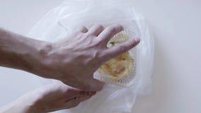 La mano del maschio non imballato il sacchetto di plastica con il dolce in contenitore e mostra il dito medio video d archivio