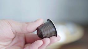 La mano del maschio tiene il piccolo baccello marrone con le bande della macchina automatica del caffè archivi video