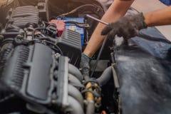 La mano del meccanico di automobile controlla il motore di automobile immagini stock libere da diritti