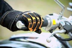 La mano del motociclista riposa sul motociclo del volante Immagini Stock Libere da Diritti