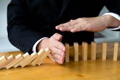 La mano del negocio para el significado volcado continuo del domin? que obstaculiz? fracaso de negocio Pare sobre este concepto d fotos de archivo libres de regalías