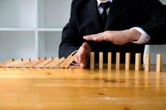 La mano del negocio para el significado volcado continuo del domin? que obstaculiz? fracaso de negocio Pare sobre este concepto d fotos de archivo