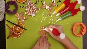 La mano del niño adorna la galleta de la Navidad del pan de jengibre almacen de video