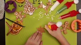 La mano del niño adorna la galleta de la Navidad del pan de jengibre metrajes