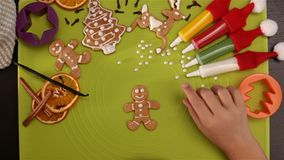 La mano del niño adorna la galleta de la Navidad del pan de jengibre con las perlas del azúcar almacen de metraje de vídeo