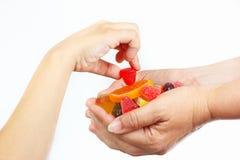 La mano del niño coge la jalea y los dulces de las manos su cierre de la madre Imágenes de archivo libres de regalías