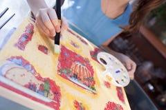 La mano del niño con el cepillo es pintura en la lona Imagen de archivo