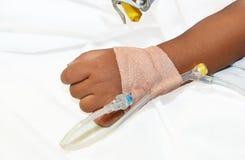 La mano del niño enfermo, intravenos fijó la infusión. Foto de archivo libre de regalías