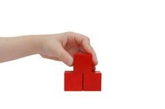 La mano del niño hace un edificio con los bloques rojos Fotos de archivo