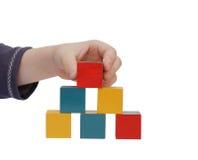 La mano del niño hace un edificio de bloques coloreados Fotos de archivo libres de regalías