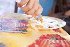 La mano del niño pone color amarillo a la gama de colores Fotos de archivo