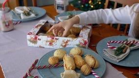 La mano del niño que alcanza hacia fuera para tomar las galletas de la Navidad almacen de metraje de vídeo