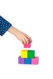 La mano del niño que construye una torre del ladrillo aislada en blanco fotos de archivo libres de regalías