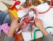 La mano del niño que hace el vestido para la muñeca hecha a mano, aprende a la costura Imagenes de archivo