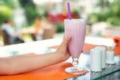 La mano del niño que sostiene el vidrio grande con el coctail sabroso fresco del batido de leche de la fresa en el café al aire l imagen de archivo libre de regalías