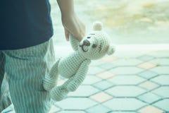 la mano del niño que sostiene un oso de peluche lindo Foto de archivo